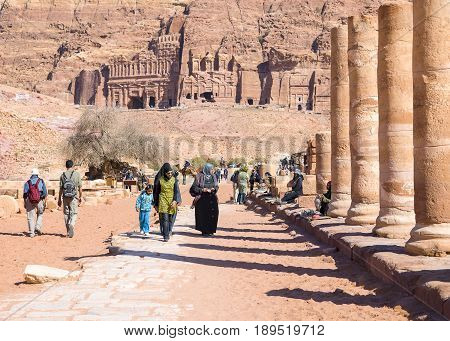 Petra Jordan - 9 March 2017: Tourists walking near ruins of the Great Temple Petra Jordan 9 March 2017