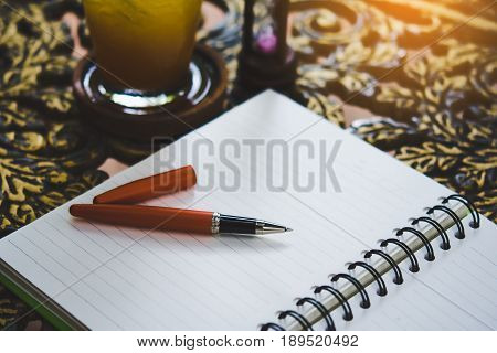 Hourglass, note pad and orange pens on the table