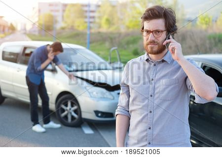 Men calling first aid after a serious car crash on the road