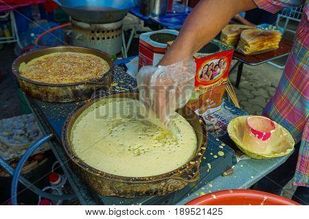 Kota Kinabalu,Sabah-May 28,2017:Street vendor preparing traditional Apam Balik or Terang Bulan cuisine at street bazaar in Kota Kinabalu,Sabah,Malaysia.It's a type of griddle pancake common in Brunei,Indonesia,Singapore & Malaysia.