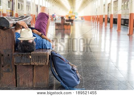 Travelers slept on chairs while waiting for the train,Hat on face with luggage on the side.