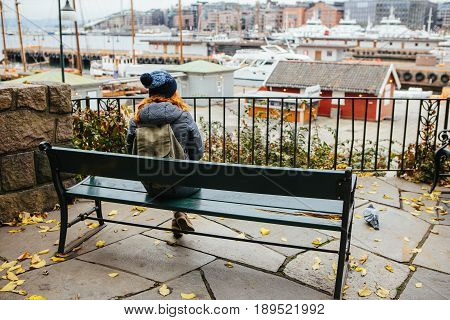 Girl traveler with a backpack looking at Oslo