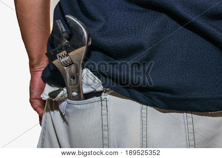 Adjustable Wrench in the pants pocket  of repairman