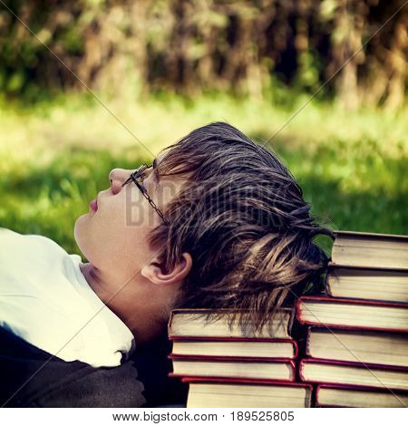 Toned Photo of Tired Teenager with a Books on the Nature Background