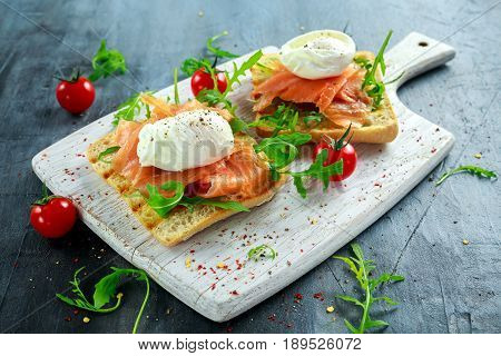 Poached egg on toast, with smoked salmon, avocado, grilled tomato, and baby spinach.