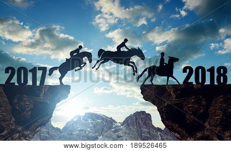 The riders on the horses jumping into the New Year 2018 at sunset.