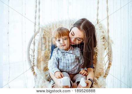 mother and son swinging on the swing at home by the window