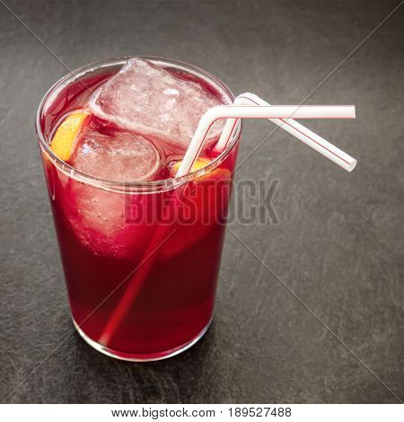 A square photo of a vibrant glass of tinto de verano, traditional Spanish summer drink, on a black background with a place for text