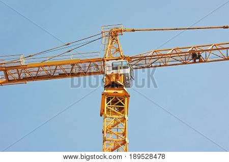 Tall construction tower crane against blue sky