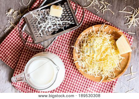 Ingredients for pasta cheese sauce or pizza, freshly grated parmesan or cheddar hard cheese, raw milk in a pot, kitchen tools, grater, wooden plate and kitchen towel, rustic vintage style, top view