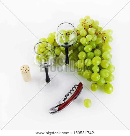 Green grapes glass goblets corkscrew and cork on a light background. Still life with grapes.