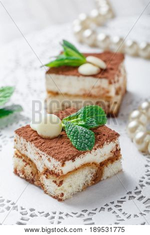 Mini cakes tiramisu with white chocolate cocoa and candies on light background close up. Delicious dessert and candy bar