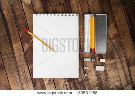 Photo of blank stationery set: album pencil case pencil flash drive clip and eraser on wood table background. Template with plenty of copy space for placing your design. Top view