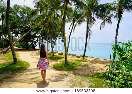 Singapore, Singapore - February 13, 2017: Tourist girl walk at the sunny Palawan Beach of Sentosa Island in Singapore.