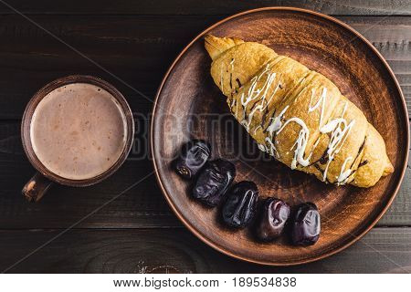 Hot chocolate or cocoa drink in cup and sweet croissant and dates fruit at plate on dark brown wooden table top view.