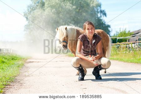 Friendship and trusting. Smiling teenage girl sitting near cute little shetland pony. Summertime outdoors image.