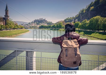 Austria. Salzburg. Girl Tourist On A Bridge Over The River Salzach Looks At The City And The Fortres