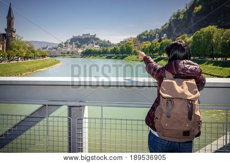 Austria. Salzburg. Girl tourist on a bridge over the river Salzach looks at the city and the fortress Hohensalzburg