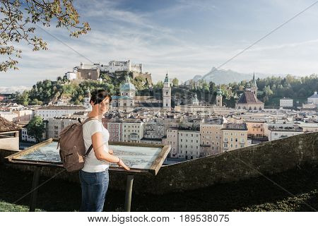 Austria. Salzburg. The Girl Tourist On The Observation Deck At The Old Maps Of The City With Views O