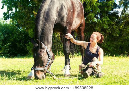 Young woman equestrian sitting close to her dark horse on green grass. Vibrant multicolored summertime outdoors horizontal image.