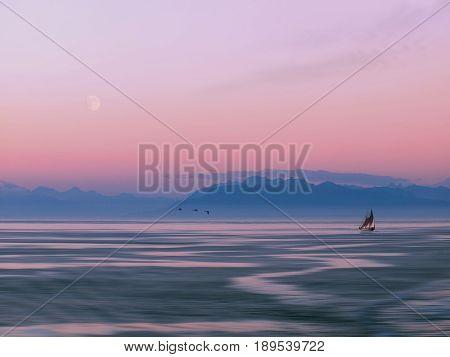 Tallship cruising against the mountain backdrop at the moonrise time