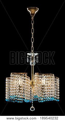 Large crystal chandelier decorated transparent and blue crystals isolated on black background. Luxury royal expensive chandelier for living room, Hall of celebration.