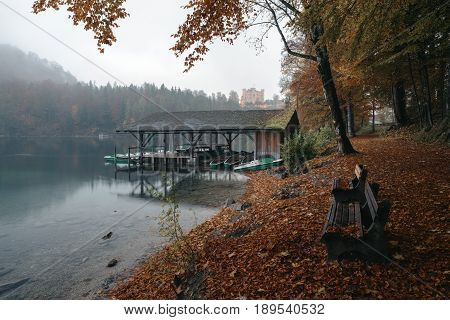 Hohenschwangau near Fussen in Bavaria Germany. Boat station on Lake Alpsee overlooking Hohenschwangau Castle surrounded by autumn forest.