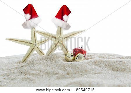 Christmas vacation concept. Two starfishes with red christmas hats and two christmas bells on the white beach sand isolated on white background