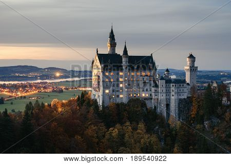 Germany. Famous Neuschwanstein Castle in the background of trees with yellow and green leaves and valley