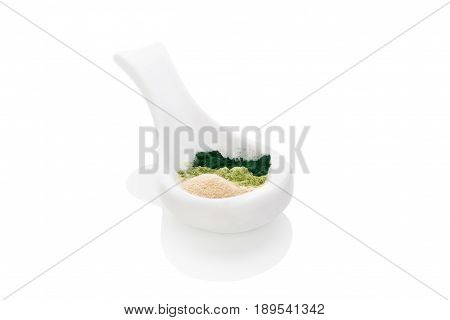 Powder supplements on white spoon. Spirulina wheat grass and ashwagandha. Detox background.