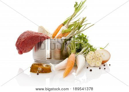Broth ingredients in silver pot isolated on white background. Bouillon cooking. Fresh vegetables in pot.