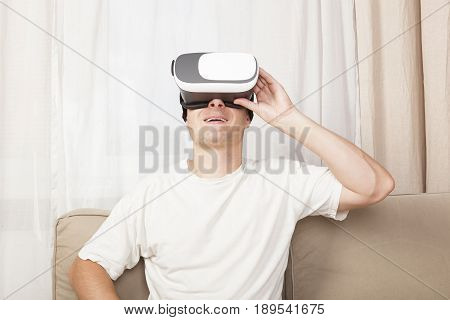 Young handsome man in Virtual Reality on sofa. Virtual reality porn.