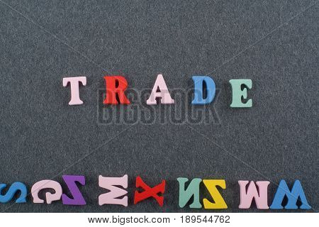 TRADE word on black board background composed from colorful abc alphabet block wooden letters, copy space for ad text. Learning english concept