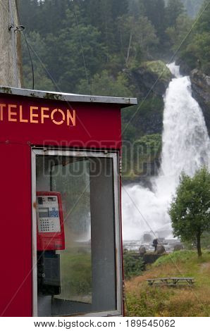 Waterfall And Red Telephonebox In Green And Beautiful Nature.
