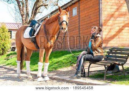 Woman riding trainer near chestnut horse speaking on mobile phone. Horizontal multicolored outdoors image.