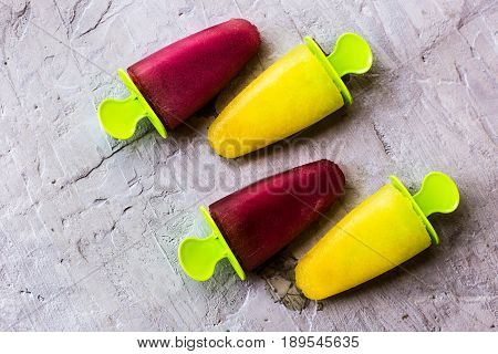 Fruit homemade ice cream lying on a neutral gray concrete background. Colorful multi-colored frozen fruit juice.