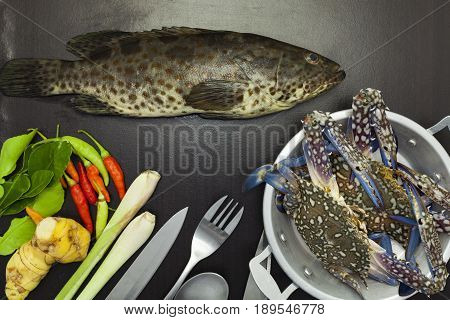 Grouper fish and crabs on dark black backgroundspices and vegetables cooking concept