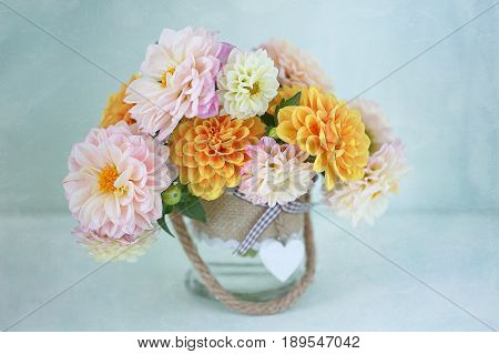 Beautiful bouquet of a yellow and pink dahlias on a light green background.