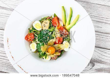 Fresh salad with tuna spinach arugula codfish artichokes quail eggs avocado cherry tomatoes physalis and sesame on wooden background close up. Mediterranean food