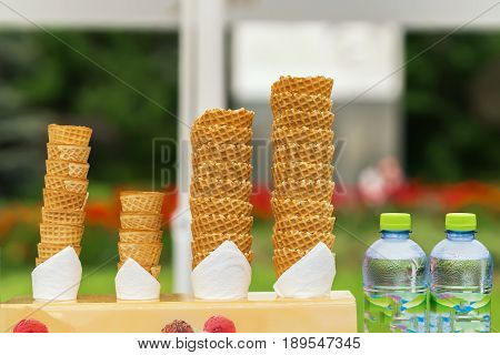 Many empty wafer sweet cornets for ice cream on naturale green blurry background. Selective focus. Copy space. Real scene in the store. Concept of summer, sweets, lifestyle