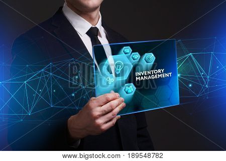 Business Technology Internet and network concept. Young businessman working on a virtual screen of the future and sees the inscription: Inventory management