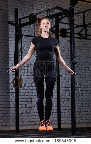 Young beautiful sporty woman working with jumping rope in cross fit gym against brick wall. Athlete woman jumping with jumping-rope. Woman in the black sportwear and orange sporty shoes. Healthy lifestyle.