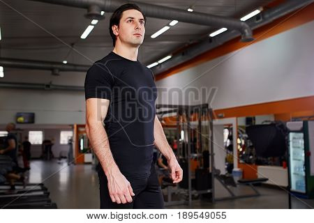 Portrait of young beautiful sportsman in the black sportwear while standing with in gym. Horizontal photo. Concentration and motivation. Sportsman in the t-shirt and shorts. Healthy lifestyle.