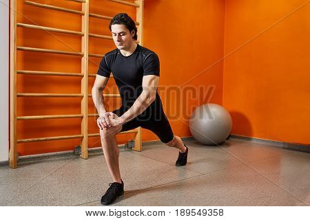 Strong young sportsman in the black sportwear stretching legs before gym workout. Man in the t-shirt, shorts and sporty shoes. Athlete doing stretching against bright orange wall in the gym. Healthy lifestyle.