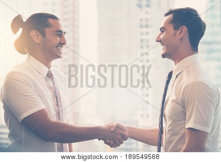 Young Businessmen handshaking after success business negotiation with skyscraper background.
