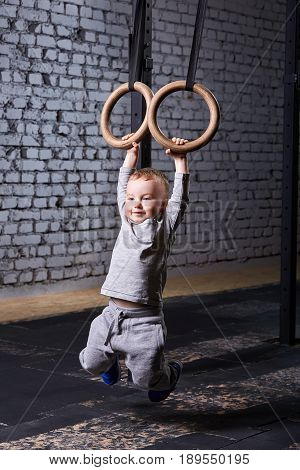 Cute child boy hanging on gymnastic rings in the cross fit gym against brick wall. Little boy in the grey sportwear. Portrait of smiling child boy. Child rearing in healthy lifestyle.