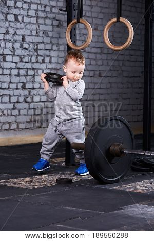 Little cute boy in sportwear standing with disk of the barbell at the gym and looking on the barbell against brick wall. Sporty child in the grey sportwear and blue sportive shoes. Child rearing in the healthy lifestyle.