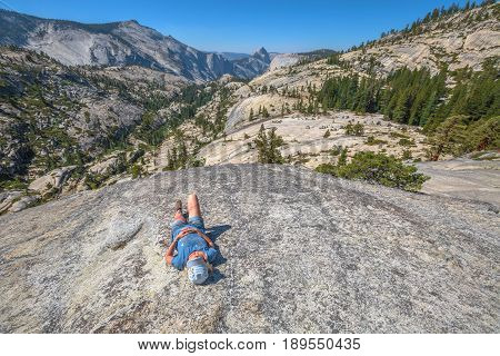 Hiking woman relaxing alone sleeping at Olmsted Point. Tired hiker resting lying down outdoors taking a break from hiking. Young caucasian woman in Yosemite National Park, California, United States.
