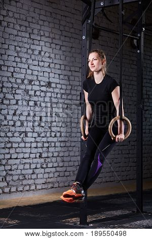 Young athletic woman doing pull-ups exercise with rings as cross fit workout against brick wall. Sporty woman in the black sportwear, t-shirt, leggings and orange sport shoes. Healthy lifestyle.