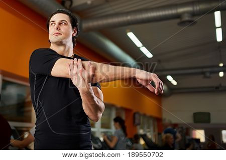 Young athlete healthy man in the black sportwear stretching shoulder before gym workout. Portrait of attractive sportsman. Horizontal cpose-up photo. Healthy lifestyle.